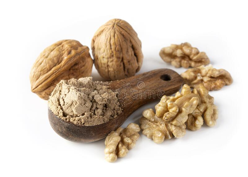Walnut flour in the wooden spoon stock images