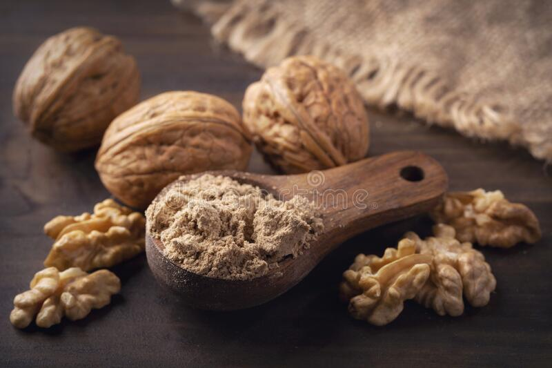 Walnut flour in the wooden spoon royalty free stock photography