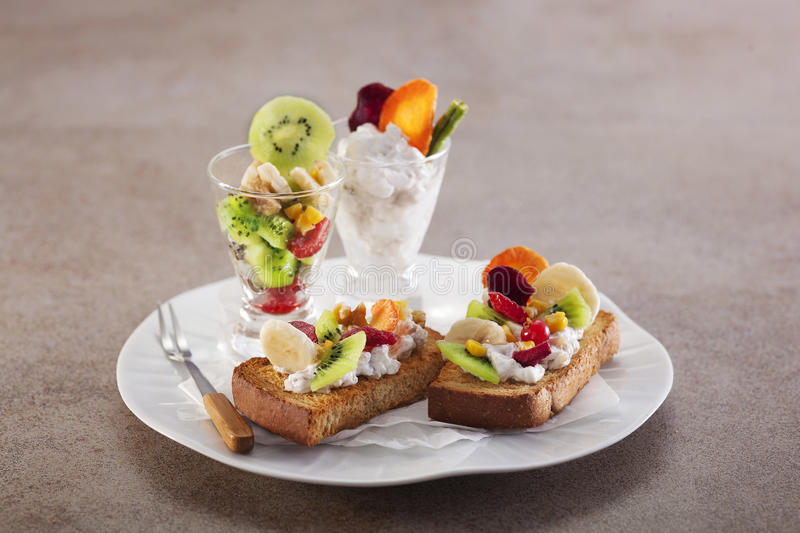 Walnut fruit cheese toast with kiwi, strawberry and banana on white plate in grey background royalty free stock photography