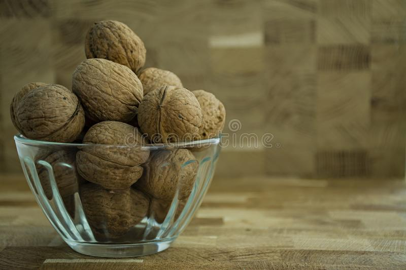 Walnut in a glass bowl on a wooden background. Side view stock photography
