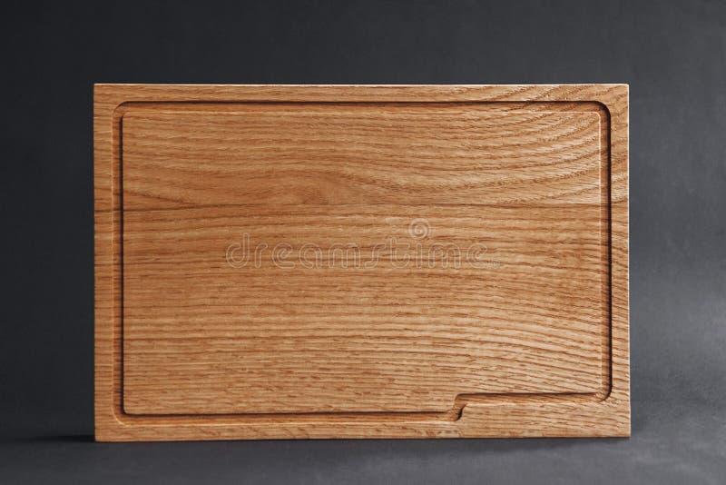Walnut handmade wood cutting board on black wooden board royalty free stock photography
