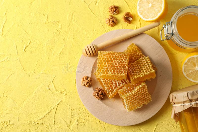 Walnut, honeycombs, jars with honey, dipper and lemon on yellow background. Copy space stock photography