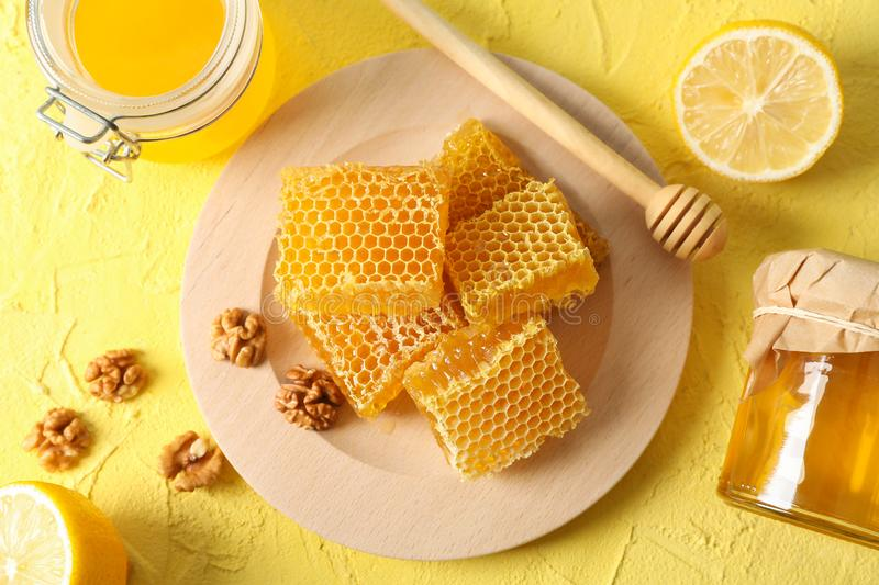 Walnut, honeycombs, jars with honey, dipper and lemon on yellow background. Top view royalty free stock photos