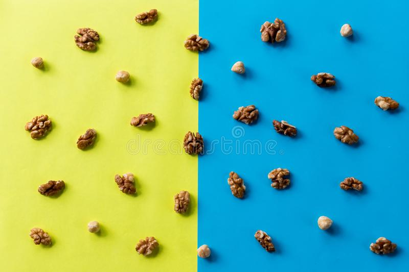 Walnut kernel pattern backdrop. One open nut shell with kernel on yellow blue background. Top view.Flat lay composition royalty free stock photo