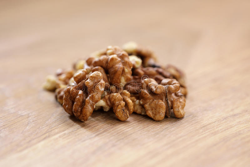 Walnut kernels on aok wood table close up. Selective focus royalty free stock photos
