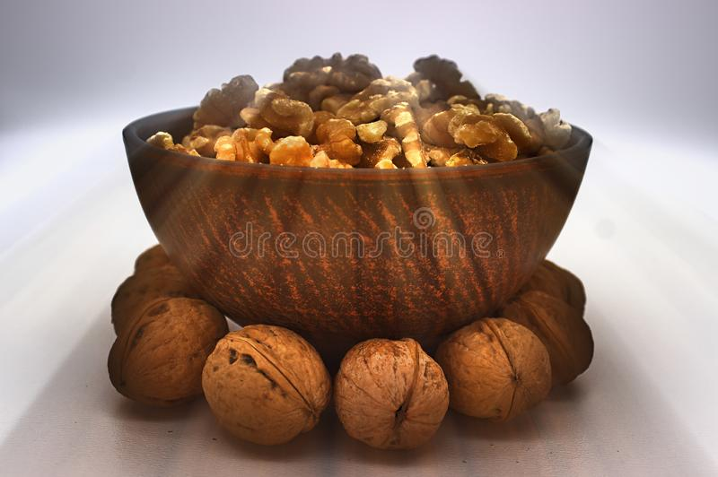 Walnut Kernels In Clay Bowl Other Names: Juglans Regia, Persian Walnut, English Walnut, Circassian Walnut. Isolated Image On A. White Background stock photography