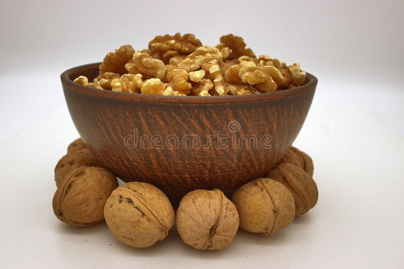 Walnut Kernels In Clay Bowl Other Names: Juglans Regia, Persian Walnut, English Walnut, Circassian Walnut. Isolated Image On A. White Background stock image