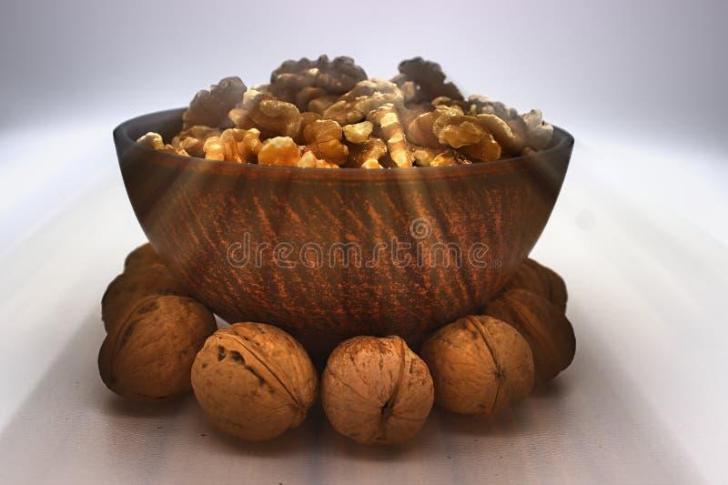 Walnut Kernels In Clay Bowl Other Names: Juglans Regia, Persian Walnut, English Walnut, Circassian Walnut. Isolated Image On A. White Background stock photos