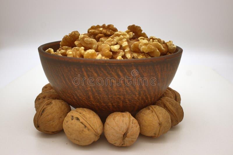 Walnut Kernels In Clay Bowl Other Names: Juglans Regia, Persian Walnut, English Walnut, Circassian Walnut. Isolated Image On A. White Background royalty free stock photo
