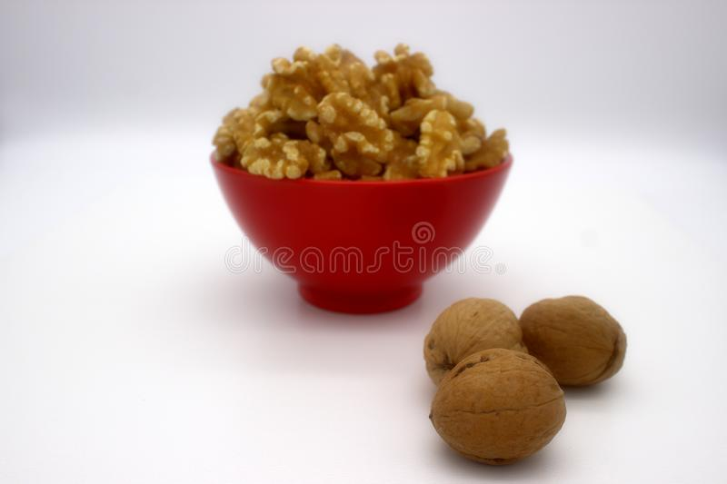 Walnut Kernels In Red Bowl Other Names: Juglans Regia, Persian Walnut, English Walnut, Circassian Walnut. Isolated Image On A. White Background stock images