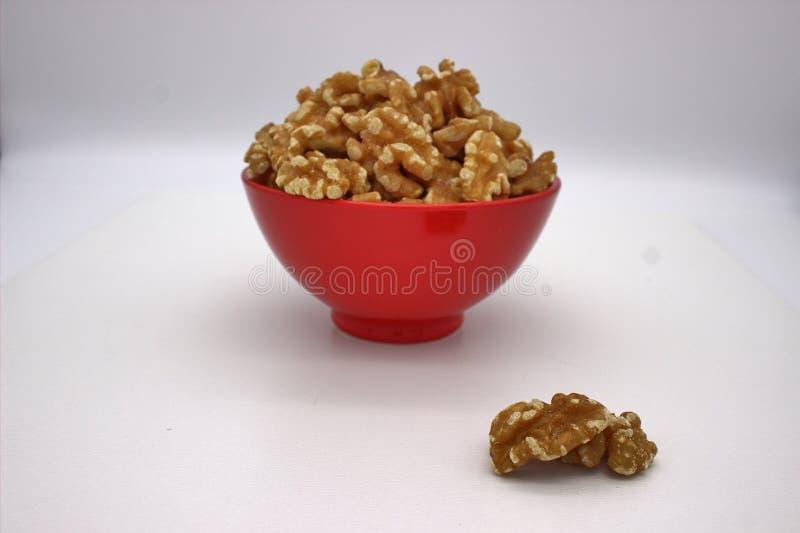 Walnut Kernels In Red Bowl Other Names: Juglans Regia, Persian Walnut, English Walnut, Circassian Walnut. Isolated Image On A. White Background stock photo