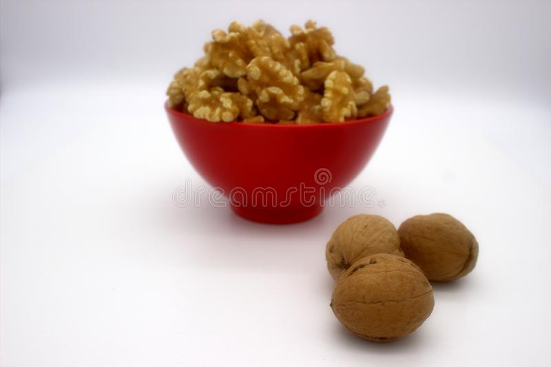 Walnut Kernels In Red Bowl Other Names: Juglans Regia, Persian Walnut, English Walnut, Circassian Walnut. Isolated Image On A. White Background royalty free stock image