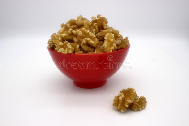 Walnut Kernels In Red Bowl Other Names: Juglans Regia, Persian Walnut, English Walnut, Circassian Walnut. Isolated Image On A. White Background stock image