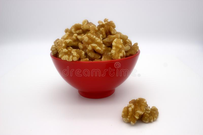 Walnut Kernels In Red Bowl Other Names: Juglans Regia, Persian Walnut, English Walnut, Circassian Walnut. Isolated Image On A. White Background royalty free stock images
