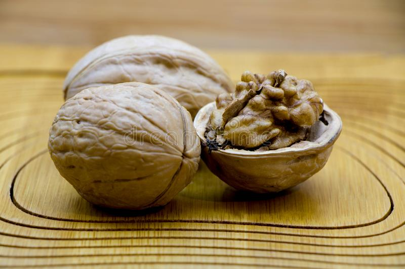 Walnut kernels and whole walnuts on rustic table. stock photography