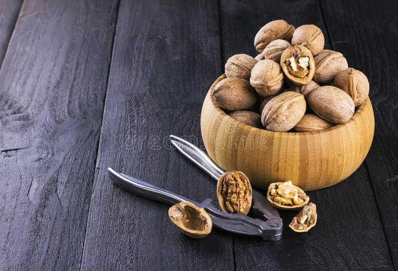 Walnut kernels and whole walnuts on wooden background stock images