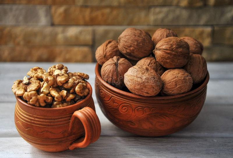 Walnut peeled and inshell in pottery on a wooden table. Walnut peeled and inshell in pottery on a white wooden table royalty free stock photos