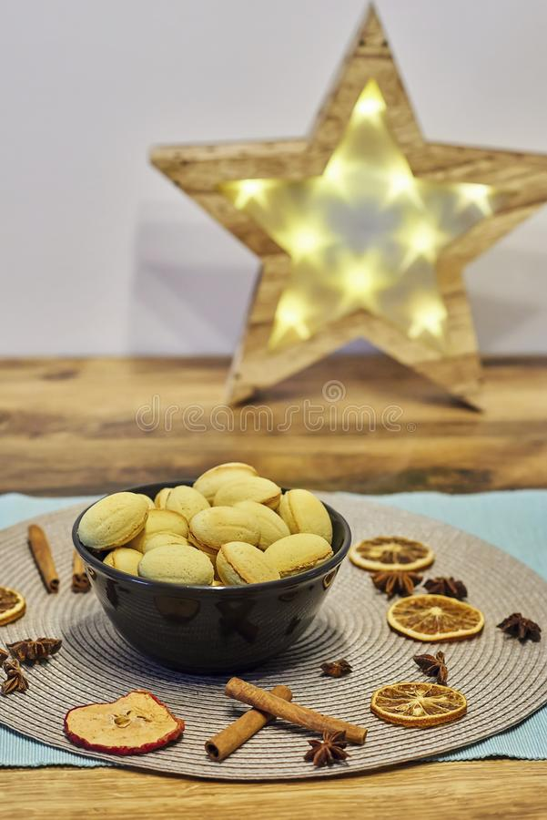 Walnut shaped butter cookies in pottery bowl, cinnamon sticks, slices of dried orange and apple, Christmas spice stock images