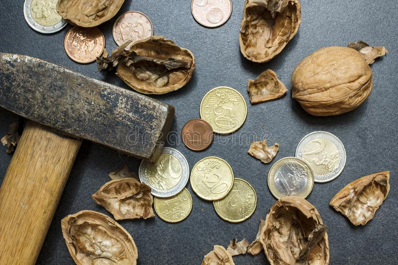 Walnut shells, euro coins and cents, lies next to a hammer. The. Concept of making money. Close-up.r royalty free stock photos
