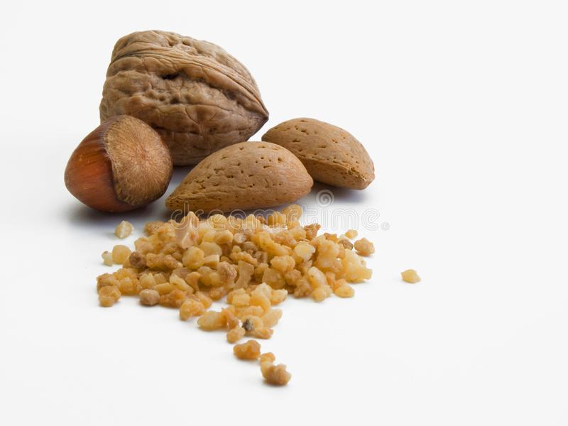 A walnut, two almonds and a hazelnut together with a small pile of the same fruits. A walnut, two almonds and a hazelnut together a small pile of crushed fruits royalty free stock photo