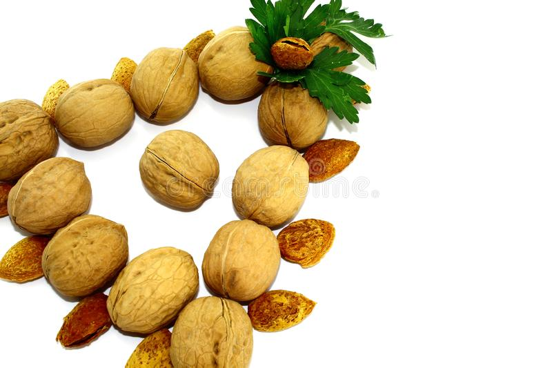 Triangle that is assembled of walnuts and almonds on a white background stock image