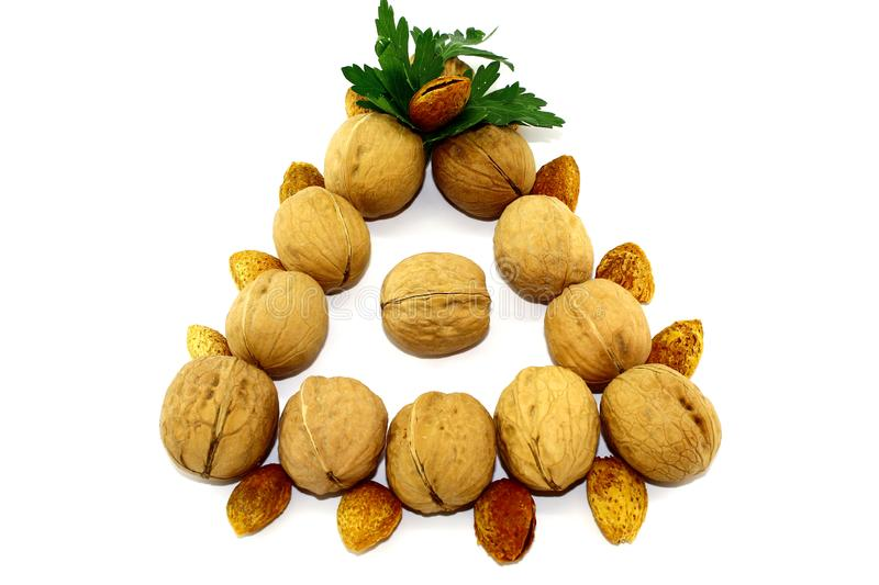 Walnuts and almonds in the shape of a triangle on a white background stock photos