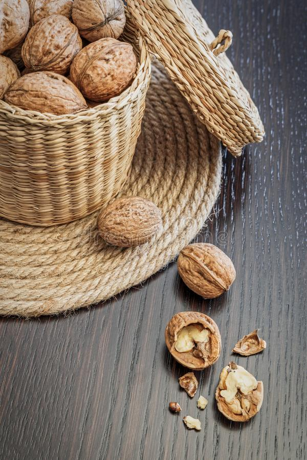 Walnuts in basket on a dark wooden table royalty free stock photography