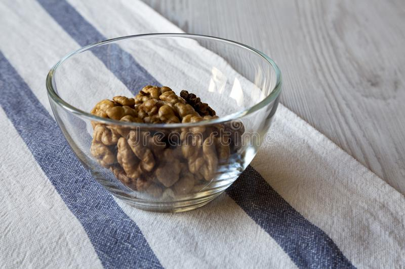 Walnuts in glass bowl on cloth over white wooden background. Closeup royalty free stock images