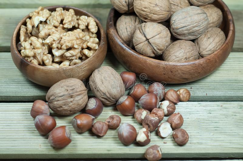 Walnuts, hazelnuts, peeled and inshell. Located on a wooden surface royalty free stock photography