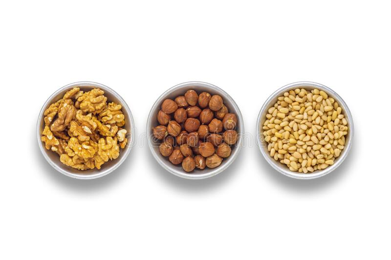 Walnuts, hazelnuts and pine nuts. In aluminum cups, on an isolated white background stock photos