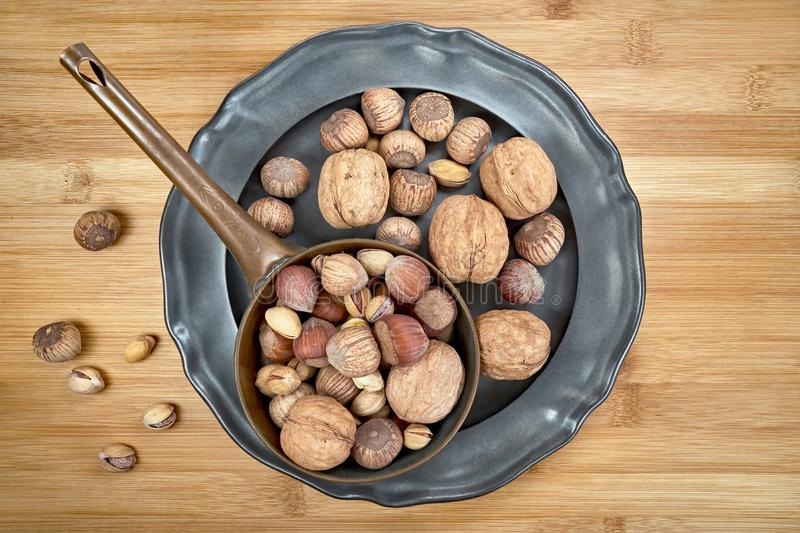 Nuts of various kinds on a metal plate, centrally from above on a wooden board stock photo