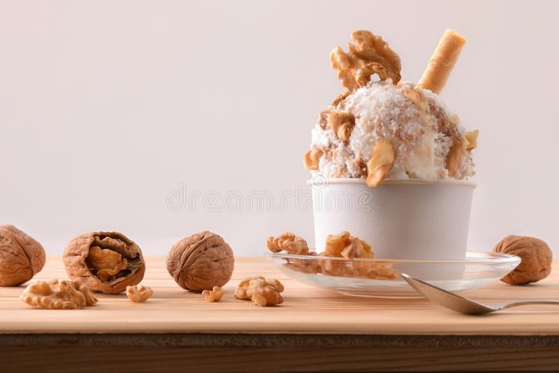 Walnuts ice cream cup decorated with pieces of nuts royalty free stock image