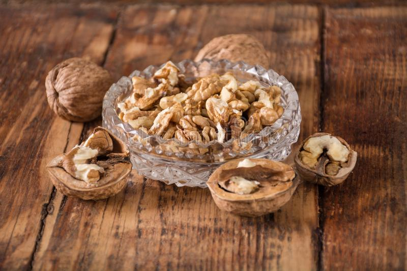 Walnuts kernel in glass bowl and spilled on retro wooden desk. Raw beautiful natural walnuts kernel in glass bowl and spilled on retro wooden desk background stock photos