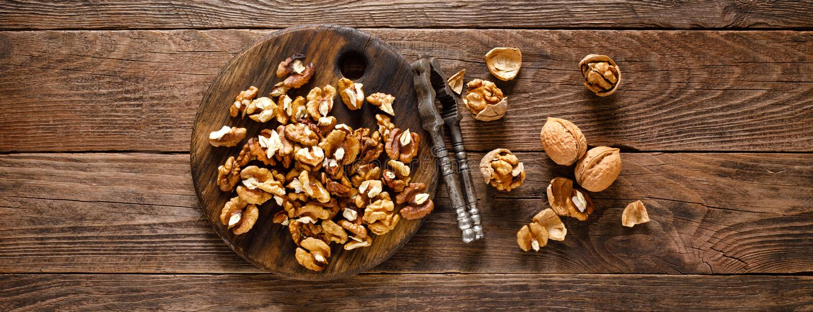 Walnuts. Kernels and whole nuts on wooden rustic table, banner closeup, top view. Walnuts. Kernels and whole nuts on wooden rustic table, banner, top view stock images