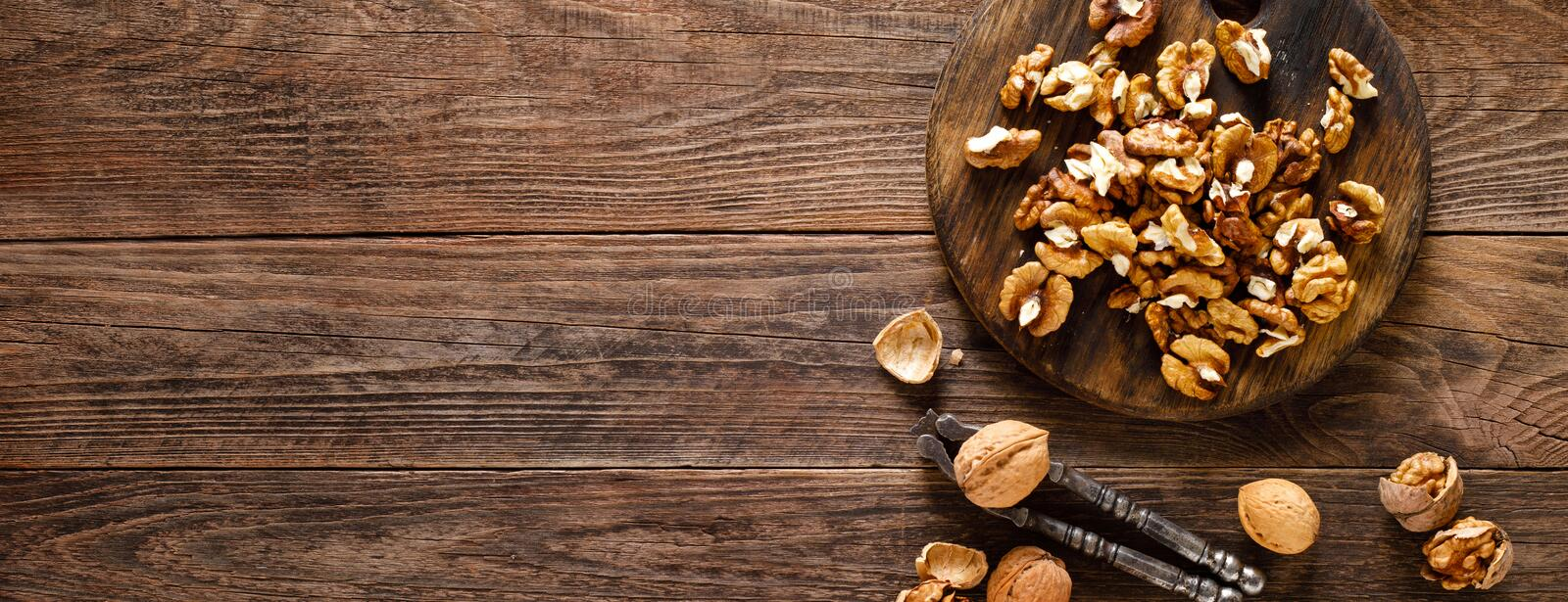 Walnuts. Kernels and whole nuts on wooden rustic table, banner closeup, top view. Walnuts. Kernels and whole nuts on wooden rustic table, banner, top view royalty free stock photos