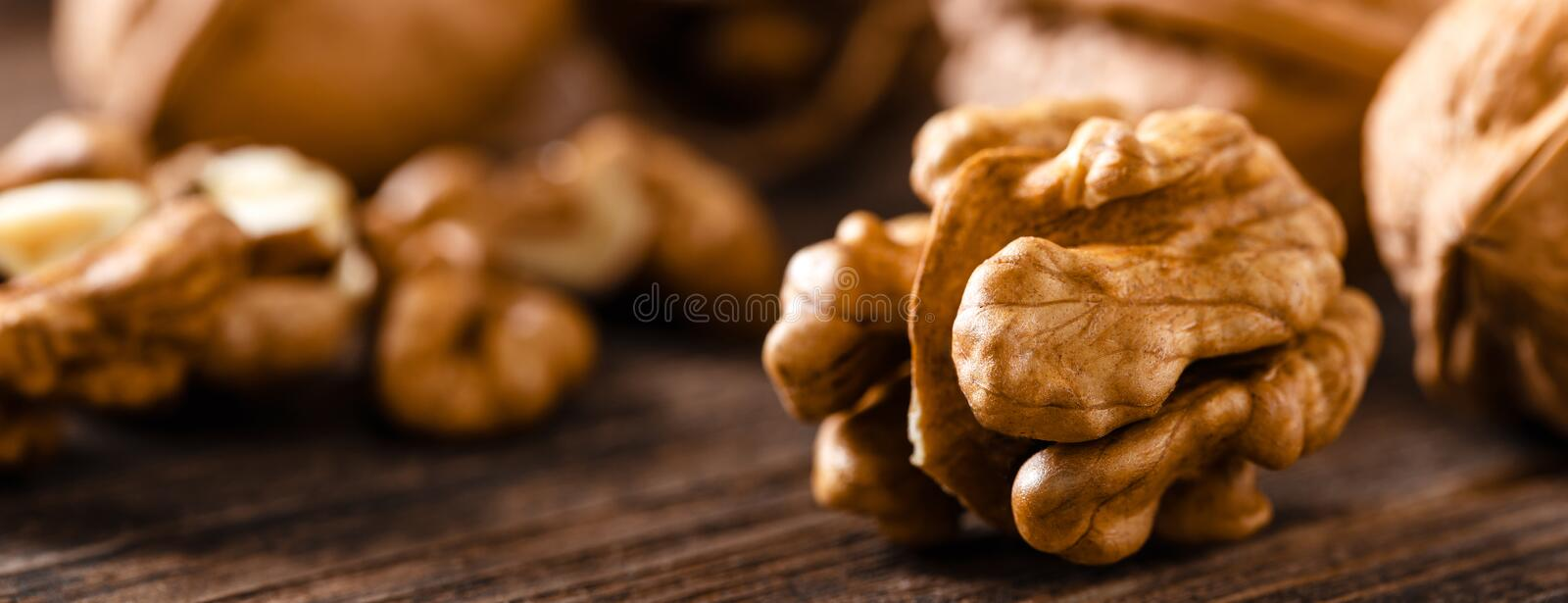 Walnuts. Kernels and whole nuts on wooden rustic table closeup, banner. Walnuts. Kernels and whole nuts on wooden rustic table, banner royalty free stock image