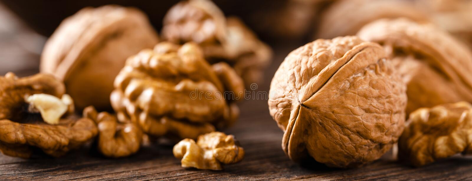 Walnuts. Kernels and whole nuts on wooden rustic table closeup, banner. Walnuts. Kernels and whole nuts on wooden rustic table, banner stock photography