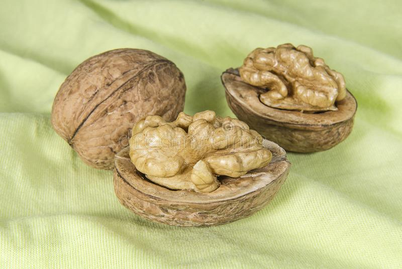 Walnuts on light green cloth. Closeup stock images