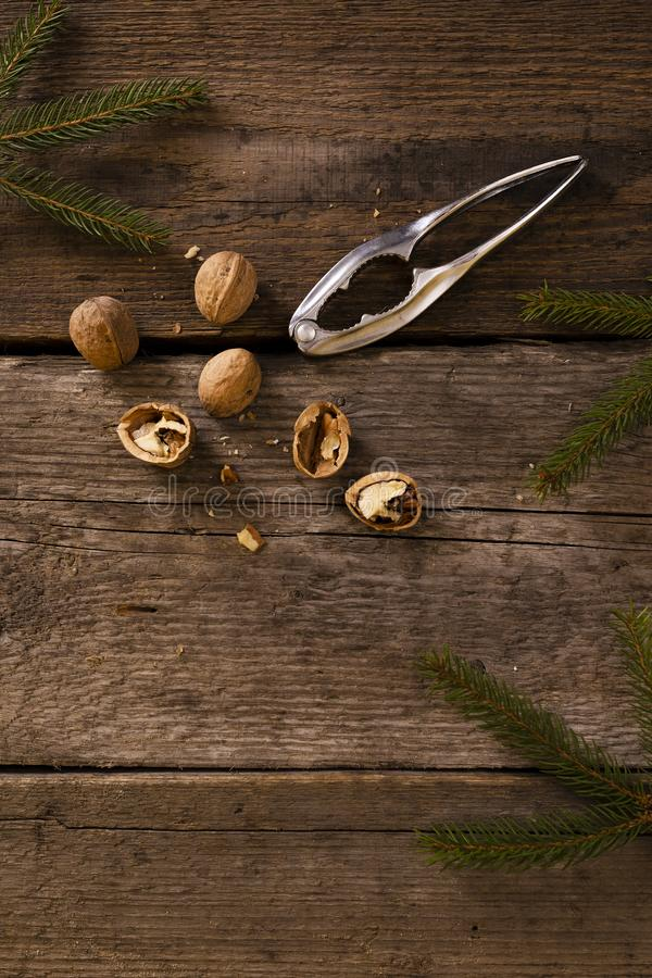 Walnuts and nutcracker on rustic wooden background. copy space for text. Around the branches of spruce. Christmas scenery stock photos