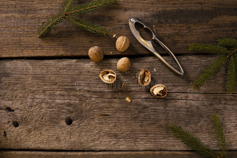 Walnuts and nutcracker on rustic wooden background. copy space for text. Around the branches of spruce. Christmas scenery royalty free stock image