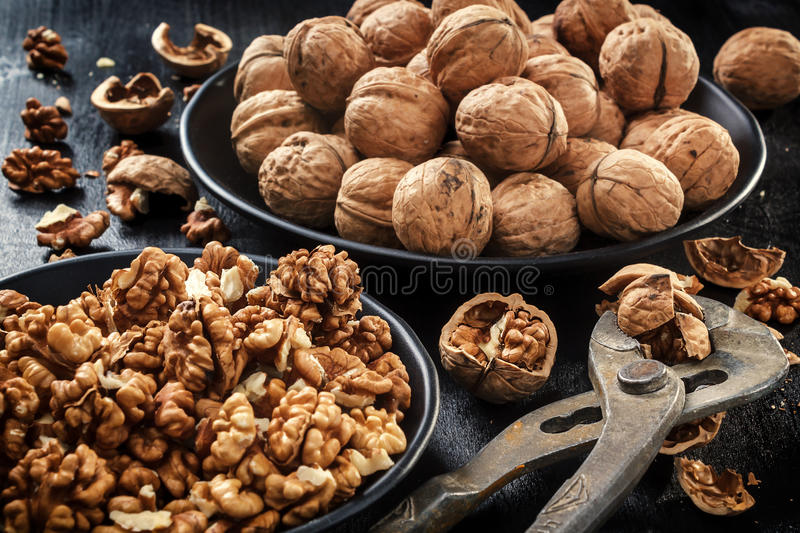 Walnuts. Nuts of walnuts. Tongs for cutting nuts. Pure organic walnuts. Walnuts. Nuts of walnuts. Nippers for cutting nuts. Scoop of walnuts. Nuts in black royalty free stock images