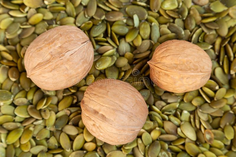 Walnuts pattern. Inshell walnut in the shell on pumpkin seeds royalty free stock photography