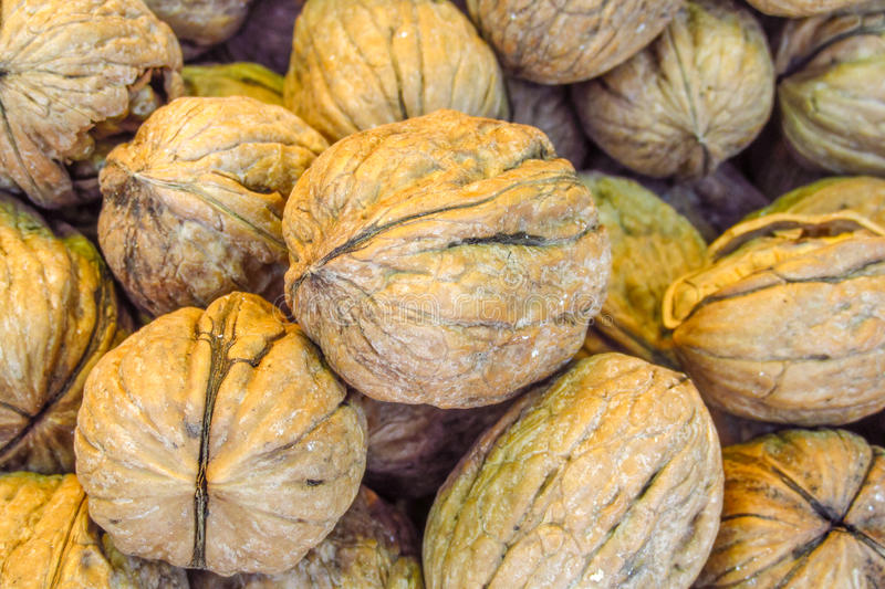 Walnuts pattern. Pile of inshell walnuts royalty free stock image