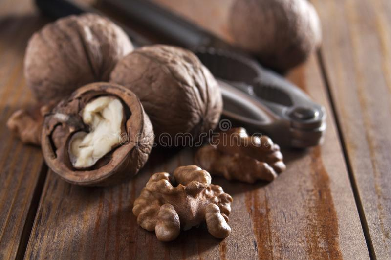 Walnuts peeled and inshell. In the background is a nutcracker. Brown wooden table.  royalty free stock photos