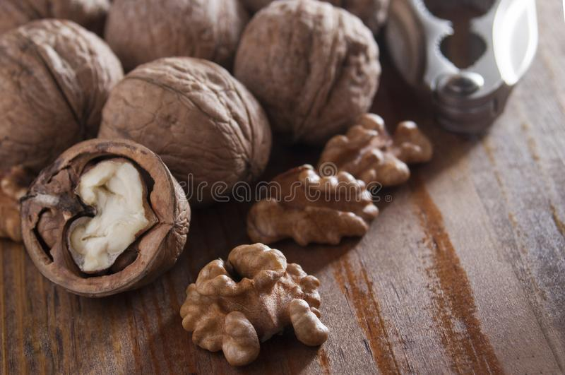 Walnuts peeled and inshell. In the background is a nutcracker. Brown wooden table. Close-up.  royalty free stock photography
