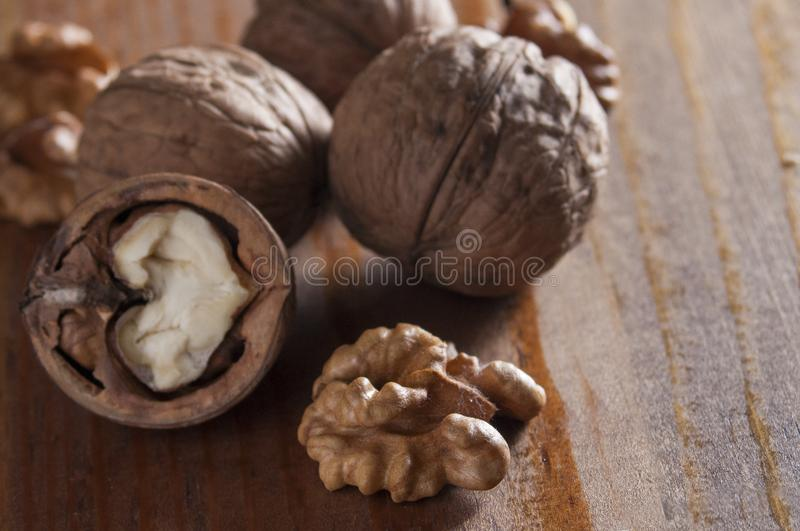 Walnuts peeled and inshell. Brown wooden background. Healthy nutrition, health care, diet. Healthy, fresh and nutritious food. Close-up royalty free stock photo