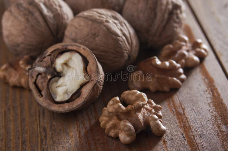 Walnuts peeled and inshell. Brown wooden background. Healthy nutrition, health care, diet. Healthy, fresh and nutritious food. Close-up royalty free stock photos