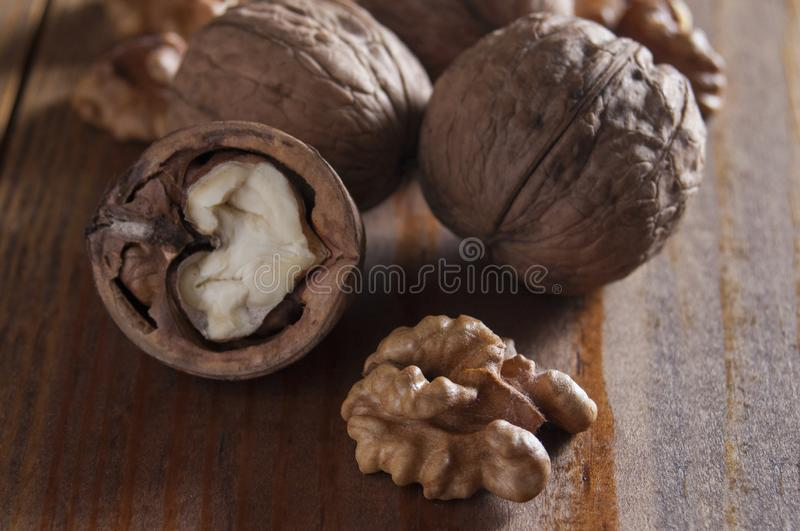 Walnuts peeled and inshell. Brown wooden table. Healthy nutrition, health care, diet. Healthy, fresh and nutritious food. Close-up. Walnuts peeled and inshell royalty free stock image