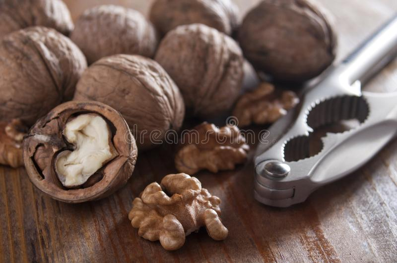 Walnuts peeled and inshell. Near a nutcracker. Brown wooden background.  stock photography