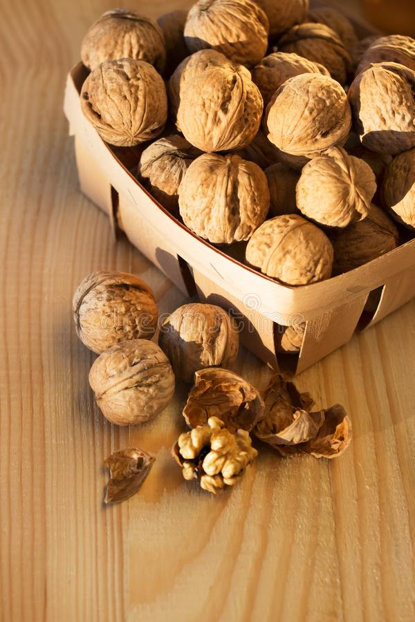 Walnuts peeled and whole on a wooden table in a natural ecological packaging basket royalty free stock images